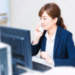 パソコンを見ながら仕事の電話をする女性