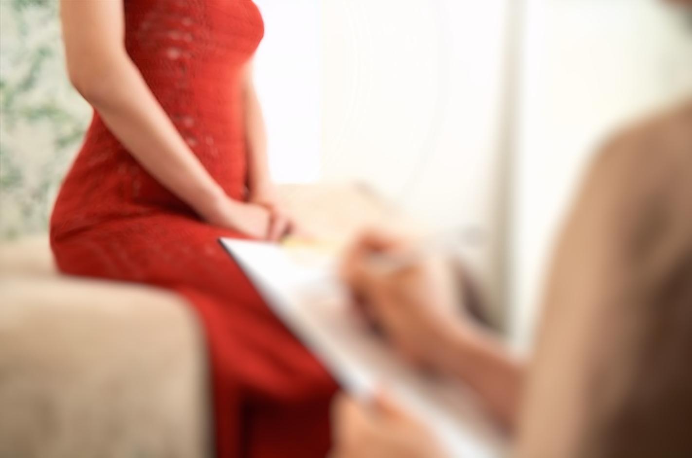 カウンセリングを受ける赤いワンピースを着た女性